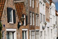 Byggnad i Middelburg, Nederländerna, detaljer av den gamla fasaden, vägg med fönster och träslutare arkivbilder