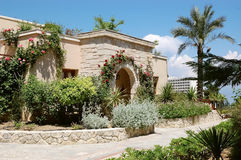 Byggnad med den välvda ingången och rosor i hotellet, Grekland royaltyfri foto