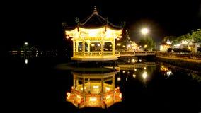 Byggnad på vattnet, trädgårds- ljus för kines på natten Royaltyfria Bilder