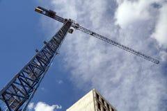 Byggnad under konstruktion, konstruktionskran mot himlen arkivbild