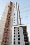 Byggnad under konstruktion med den utsatta hissen Royaltyfri Fotografi