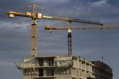Byggnad under konstruktion med kranar mot himlen arkivfoto
