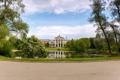 Byggnaden är av rosa tegelsten med vita kolonner på kusten av dammet Royaltyfria Bilder