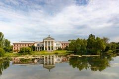 Byggnaden är av rosa tegelsten med vita kolonner på kusten av dammet Arkivbild