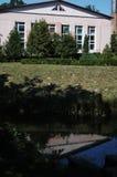 Byggnaden över vattnet med träd och reflexion av det yrkesmässiga laboratoriumet Arkivbild
