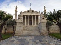 Byggnaden av Atenakademin en marmorkolonn med skulpturer av Apollo och Athena, Socrates och Plato mot a med molnet royaltyfri foto