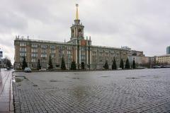 Byggnaden av den Sverdlovsk kommunfullmäktigen med stenlagt område på en molnig dag Arkivfoto