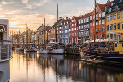 Byggnader, arkitektur och fartyg längs Nyhavnen på solnedgången royaltyfria foton