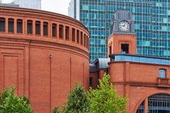 Byggnader av Stary Browar med ett klockatorn och en fasad av en modern kontorsbyggnad Royaltyfri Foto