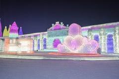 Byggnader för is och för snö för Harbin isfestival 2018 - förälskelsehjärtor -, gyckel som åka släde, natt, loppporslin royaltyfria bilder