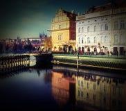 Byggnader i Prague med folk och den Vltava floden Fotografering för Bildbyråer