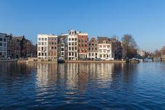Byggnader längs den Staalkade gatan och den Amstel kanalen Royaltyfri Bild