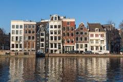 Byggnader längs den Staalkade gatan och den Amstel kanalen Arkivfoton