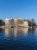 Byggnader längs den Staalkade gatan och den Amstel kanalen Royaltyfri Fotografi