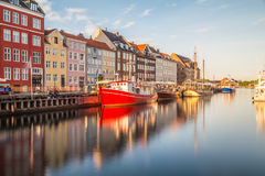 Byggnader längs Nyhavnen i Köpenhamn och ett berömt rött fartyg arkivbilder