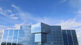 Byggnader med en glass fasad och moln för tidschackningsperiod arkivfilmer