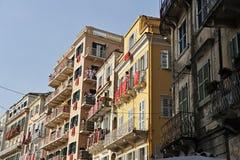 Byggnader med röda baner i Korfu arkivfoton