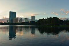 Byggnader och skogen reflekterade i sjön i härlig solnedgång på Eola sjön parkerar arkivfoto