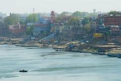 Byggnader på banken av det heliga Gangeset River i ottan på soluppgång i Varanasi, Indien royaltyfria foton