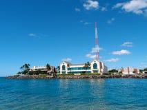 Byggnader sid på vatten kantar skyddat av en lava vaggar havsväggen Royaltyfria Foton