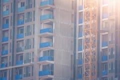 Byggnader under konstruktion med den gula konstruktionskranen slapp fokus Arkivbild
