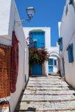 Byggnaderna av den vita blåa staden med en stentrappuppgång och en lykta arkivfoto