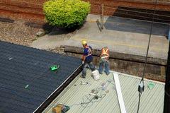 Byggnadsarbetare för två roofer som arbetar på det tenn- taket Arkivbild