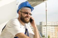 Byggnadsarbetare i arbetsdräkt och hjälm på huvudet som talar på telefonen Arbete på hög höjd Material till byggnadsställning i b Arkivbilder