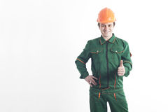 Byggnadsarbetare i arbetsorder och en hjälm som rymmer en thum Arkivfoton