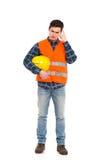 Byggnadsarbetare i den gula hjälm- och apelsinwaistcoaten som skrapar huvudet. Arkivfoton