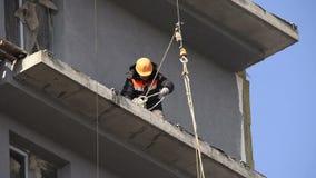 Byggnadsarbetare i en gul hård hatt lager videofilmer
