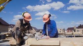 Byggnadsarbetare i likformig för säkerhet för konstruktionsplats gem Två byggmästare i en hjälm på konstruktionsplatsen stock video