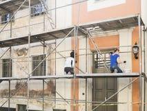 Byggnadsarbetare i material till byggnadsställning av den gamla byggnadsfasaden för återställande och renoverar Royaltyfri Foto