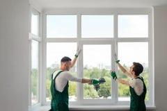Byggnadsarbetare installerar ett fönster arkivbild