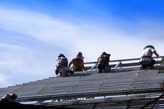 Byggnadsarbetare installerar ett ståltak Arkivbilder