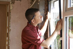 Byggnadsarbetare Installing New Windows i hus Royaltyfri Foto