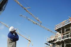 Byggnadsarbetare, kranar och material till byggnadsställning Royaltyfri Fotografi