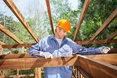 Byggnadsarbetare Measuring Timber Frame Royaltyfri Fotografi