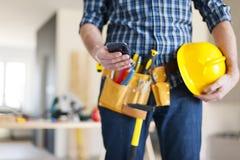 Byggnadsarbetare med den smarta telefonen arkivbild