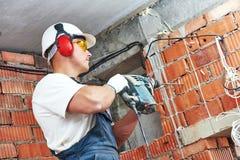 Byggnadsarbetare med drillborrhålapparaten Fotografering för Bildbyråer