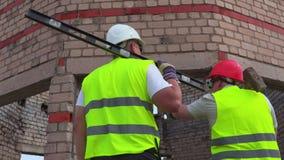 Byggnadsarbetare med hjälpmedel som talar nära oavslutad byggnad arkivfilmer