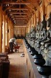 Byggnadsarbetare med rad av Buddhabilder Arkivfoto