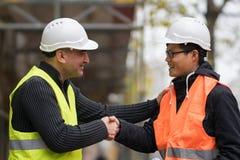 Byggnadsarbetare- och asiatarkitekt som skakar händer på konstruktionsplats Fotografering för Bildbyråer