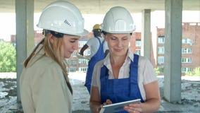 Byggnadsarbetare och tekniker som arbetar på byggnadsplats, genom att använda den digitala minnestavlan arkivfilmer