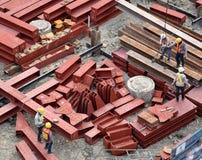 Byggnadsarbetare och teknikerer som bär säkerhetshjälmen och den enhetliga koncentraten på att lyfta rött strukturellt stål, geno arkivbilder