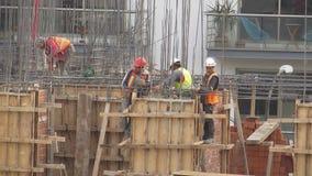 Byggnadsarbetare på byggnadsplats lager videofilmer