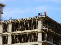 Byggnadsarbetare på det nya flerfamiljshuset arkivbilder