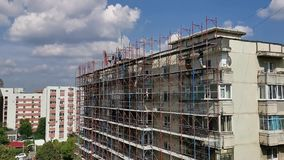 Byggnadsarbetare på materialet till byggnadsställning - byggnad av lägenheter arkivfilmer