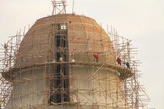 Byggnadsarbetare på materialet till byggnadsställning runt om pagod Arkivfoton