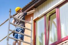 Byggnadsarbetare på materialet till byggnadsställning som målar trähusfasaden Royaltyfri Bild